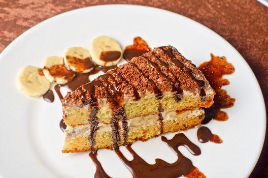 Dessert cake closeup with banana at plate