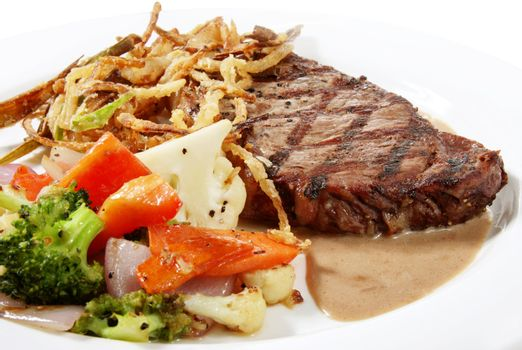grilled ny steak plated with crispy vegetables