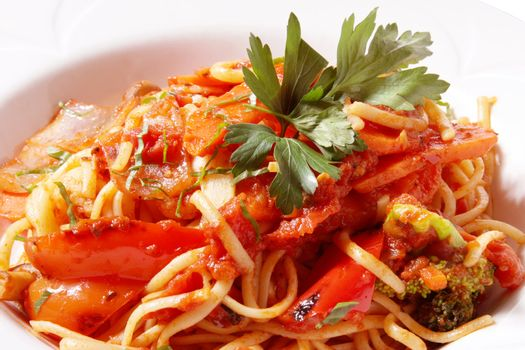 closeup of linguini pasta primavera in tomato sauce