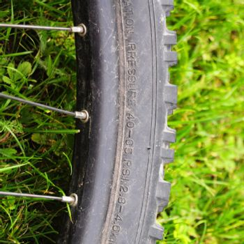 mountain bike offroad tire in green grass showing sport in nature concept