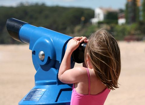 The little girl looks in a telescope