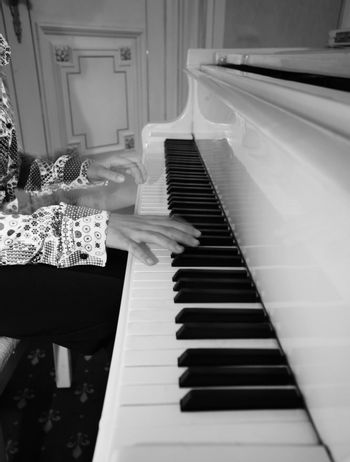 The image of the piano and child's hands. b/w
