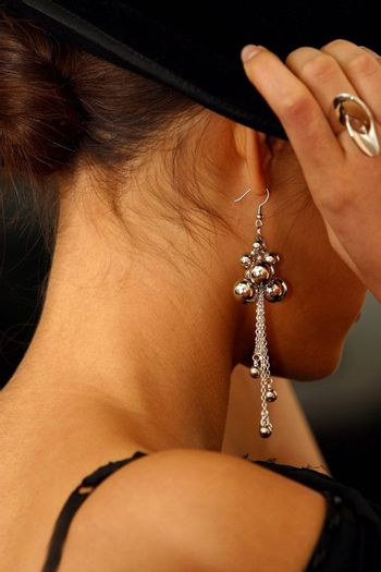 The image of the girl in rings and ear rings putting on a hat