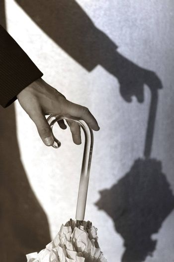 The man leans on the handle of a umbrella