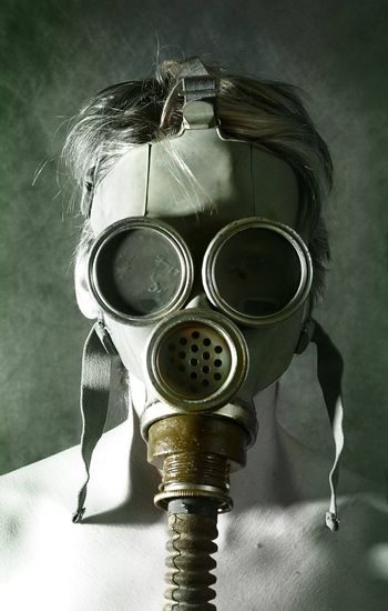 The person in a gas mask holds hands a head