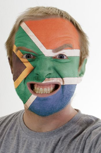 High key portrait of an angry man whose face is painted in colors of south african republic flag