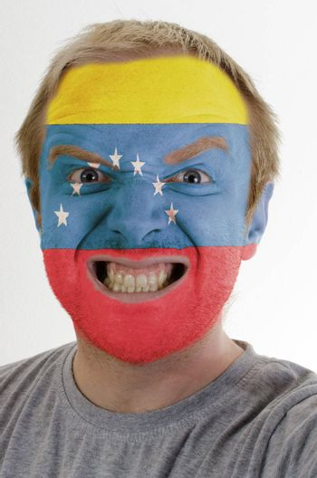 High key portrait of an angry man whose face is painted in colors of venezuela flag