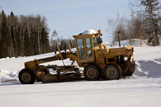 grader at work on logging road in winter