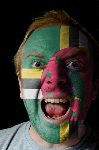 Low key portrait of an angry man whose face is painted in colors of dominica flag