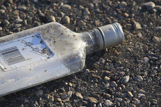 Discard liquor bottle beside road