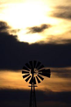 Old windmill generator against darkened sky