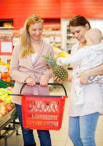 Two friends in grocery store buying groceries with baby