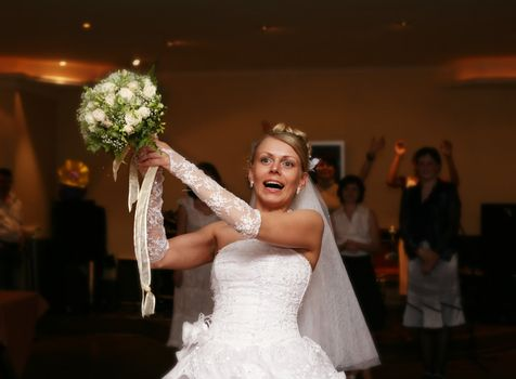 The bride throws a wedding bouquet to the girlfriends