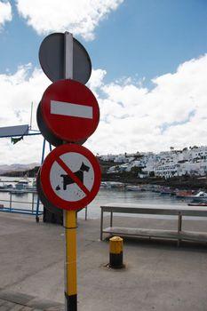 sign posts overlooking an old lanzarote harbour