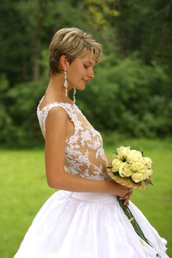 Beautiful the bride with a bouquet in park
