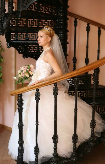 The beautiful bride with a bouquet in an interior