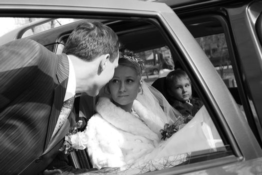 The bride with the little boy in the machine and seeing off groom. b/w
