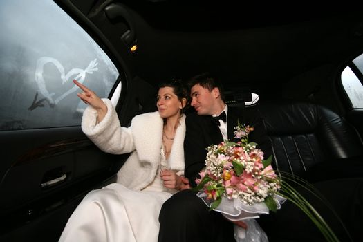 The bride draws heart on glass of the automobile