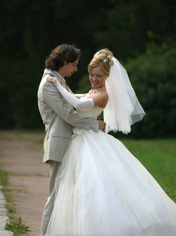 Beautiful the bride and the groom dance in a summer park