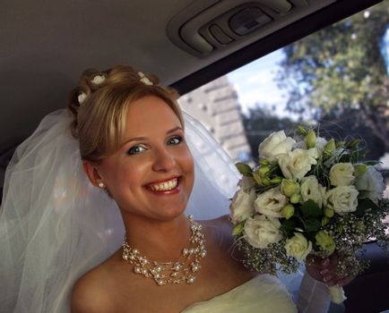 Beautiful the bride with a bouquet in the automobile