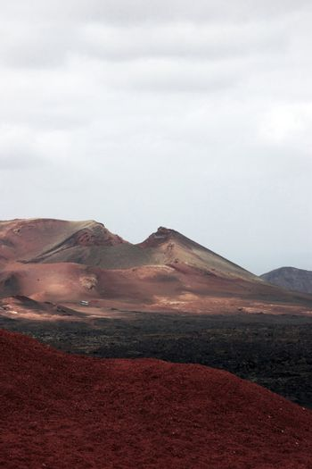a bus travelling  on the volcanic landscape