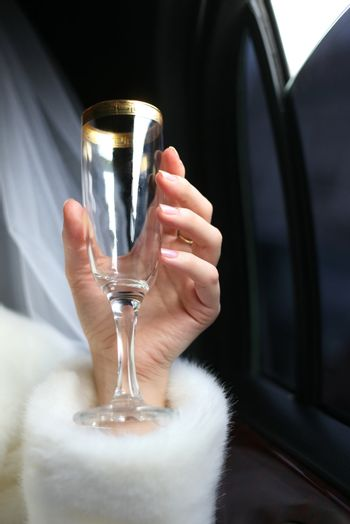 Glass with champagne in a hand of the bride