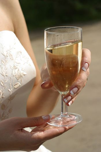 Glass with champagne in hands of the bride