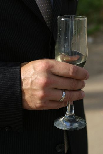 Glass of champagne in a hand of the groom