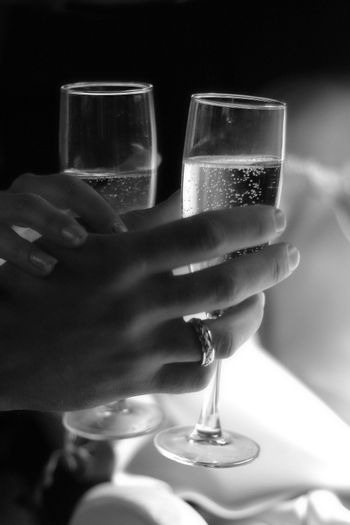 Glass of champagne in a hand of the groom and bride. b/w