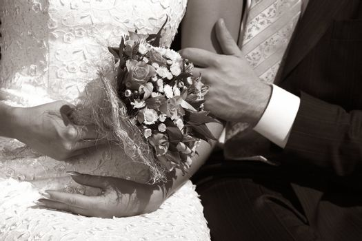 Wedding bouquet in hands of the bride. b/w+sepia