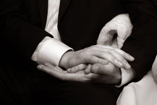 Female hands in man's hands on a dark background. b/w+sepia