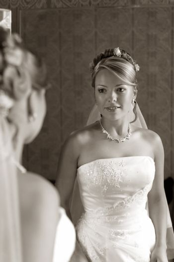 The beautiful bride looks at itself in a mirror. b/w+sepia