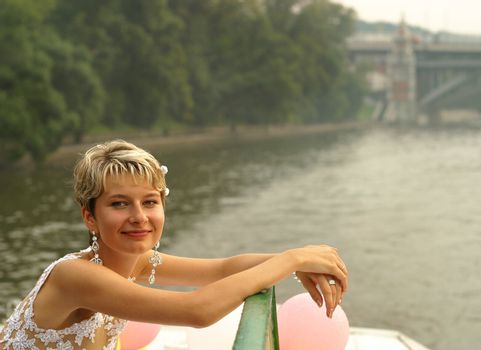 Smiling bride stands by the steam-ship