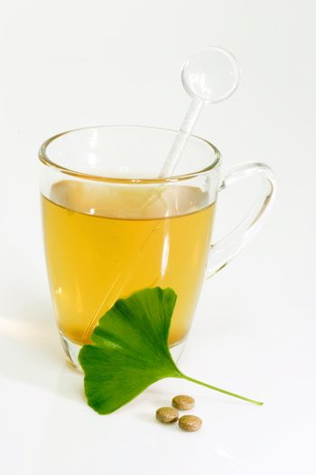 Ginkgo Biloba extract pills and fresh Ginkgo Biloba leaves with a glass of tea.