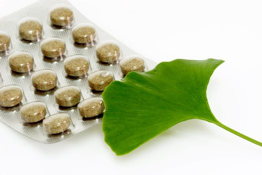 Ginkgo biloba leaf with pills on bright background.