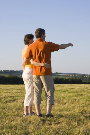 Couple standing in a meadowan hugging. The man is pointing with his outstretched arm.