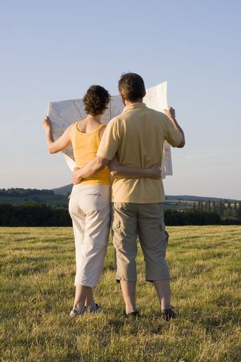 Couple looking at a map or plan in a meadow