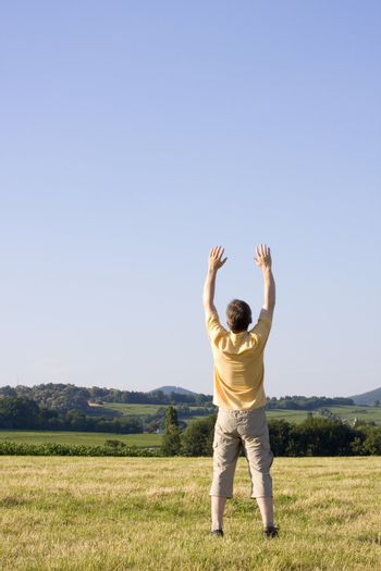 Happy man standing with uplifted arms in a meadow