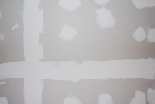 A sheetrock or drywall background.  The taping and spackling have been done in this shot.