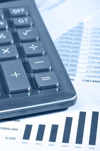 The calculator and the financial report. A workplace of the businessman