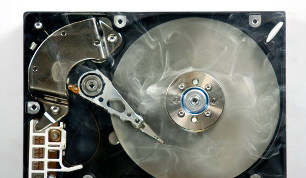 Defect hard disk drive with smoke. Open drive as symbol for data loss.