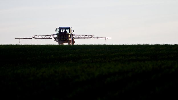 tractor spraying agricultural pesticide on field