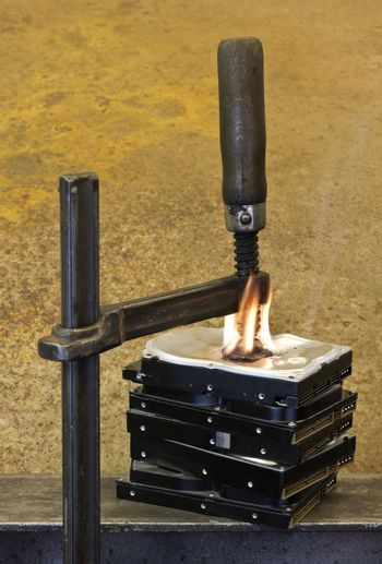 clamp pressing on burning stack of hard drives. Rusty Background