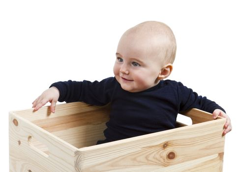 single toddler in wooden box looking to the left.