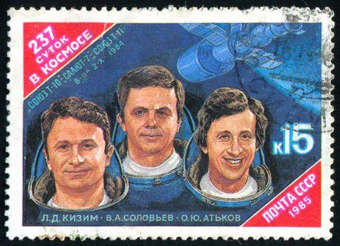 RUSSIA - CIRCA 1985: stamp printed by Russia, shows Cosmonauts L. Kizim, V. Soloviov, O. Atkov and Salyut-7 Spacecraft, circa 1985.