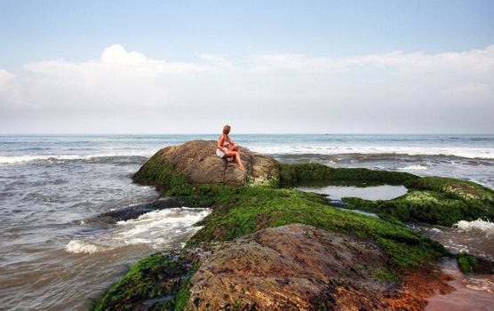 The woman sitting on a stone at ocean. Sri Lanka