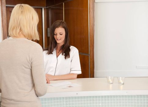 A woman in a spa recpetion deciding on a treatment