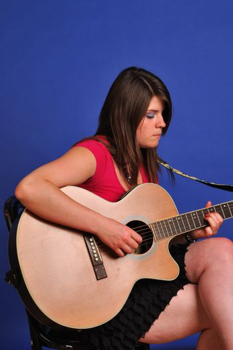 pretty girl in skirt sitting playing guitar