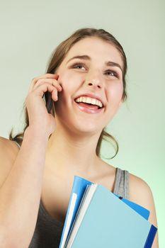 Smiling teenager girl holding blue plastic folders speaks on cellphone
