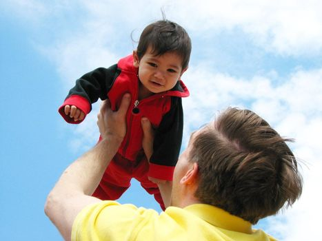 Father holding up his baby boy towards the sky